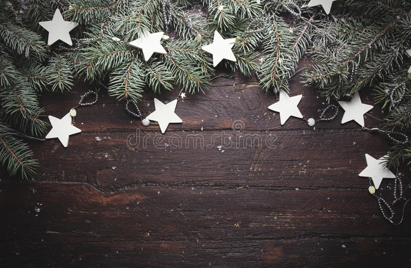 Christmas or New Year background: fur-tree branches, decoration and glittering stars on wood, top view, copy space stock photos