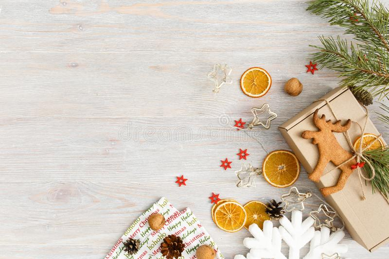 Christmas or New Year background with gingerbread deer cookie, nuts, fir tree branch, garlands, dried oranges, cones and royalty free stock photos