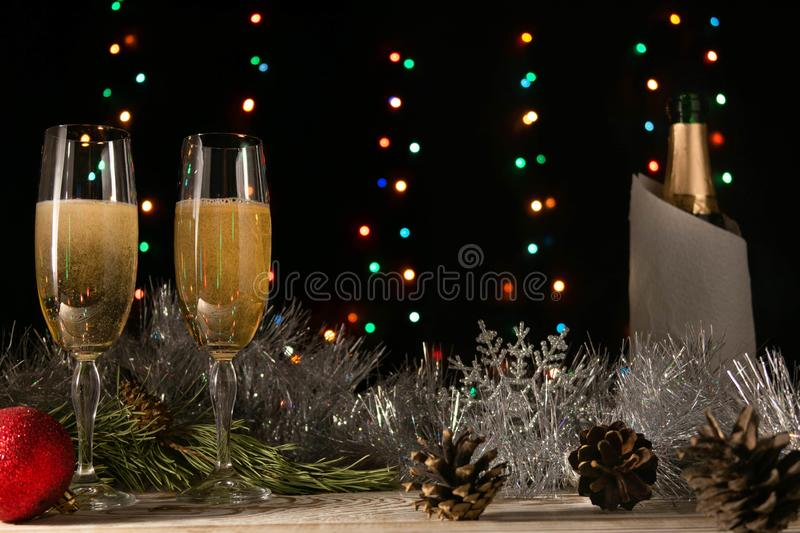 Christmas and New Year background. Romantic dinner of a couple in love with two glasses of champagne. Silver tinsel and spruce. Christmas and New Year royalty free stock image