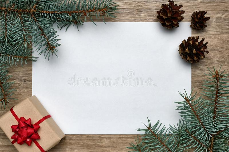Christmas or New Year background. White sheet of paper with copy space, gift box and Christmas tree branches on wood royalty free stock photo