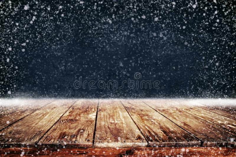 Christmas and New year background with wooden deck table and snowfall. stock photography