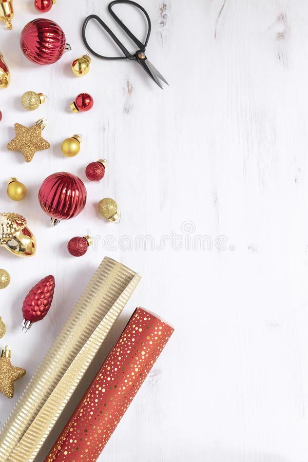 Christmas, new year background - Wrapping paper, scissors and christmas red and gold deco baubles gifts. Christmas, new year background - Wrapping paper royalty free stock photography