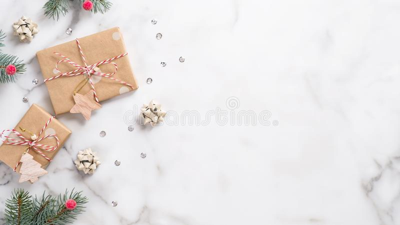 Christmas or New Year banner. Xmas greeting card. Christmas gifts and fir tree branches on white marble background. Flat lay, top stock image