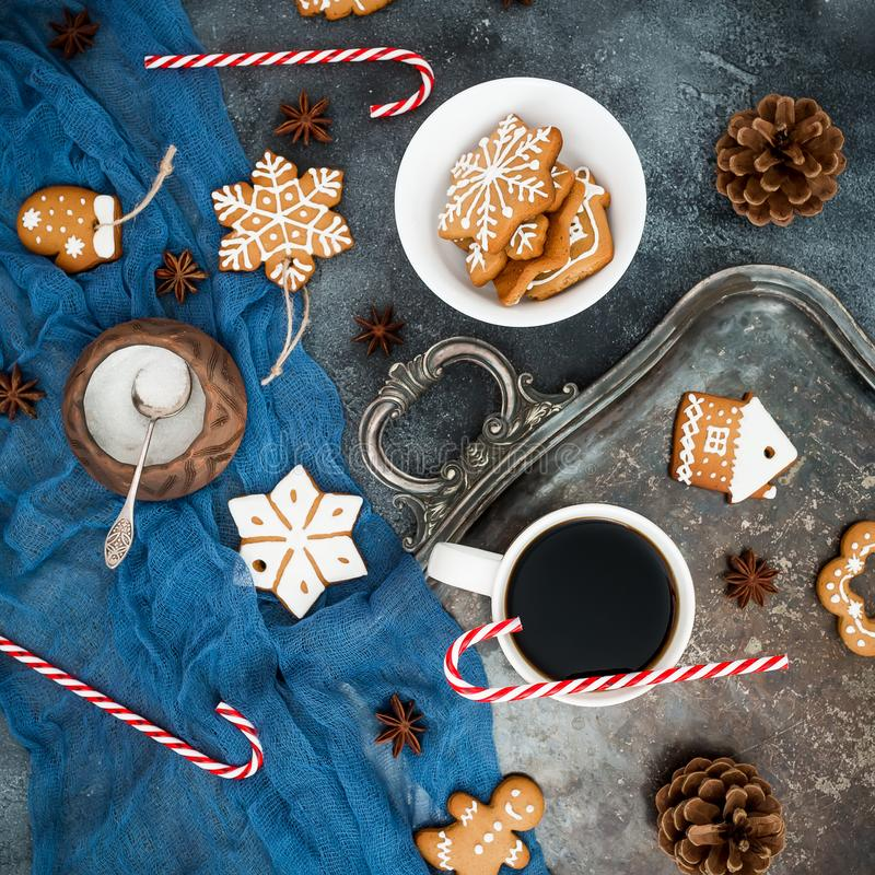 Christmas or New year breakfast. Gingerbread, candy cane and coffee cup on dark background. Flat lay. Top view stock photography
