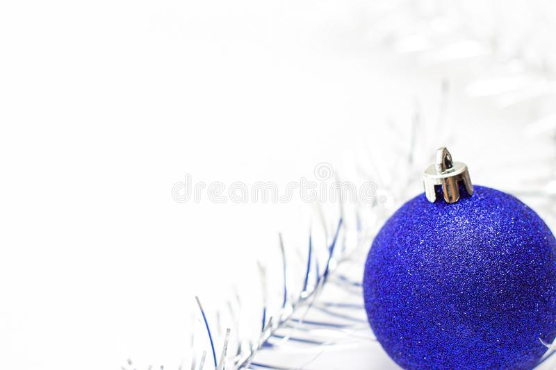 Christmas and new year card with blue ball and silver tinsel on white background. copyspace - holidays, winter and celebration con. Holidays, winter and royalty free stock image