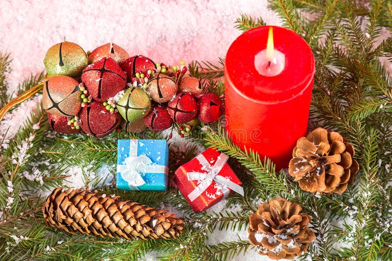 Christmas or New Year card. Burning red candle, cones, giftboxes, toys on fir tree branches and snow. Close up image royalty free stock photos