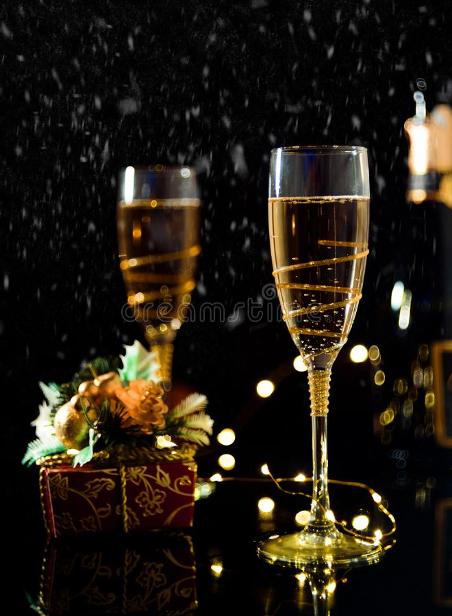 Christmas and New Year celebration with champagne. New Year holiday decorated table. Two Champagne Glasses, vintage toned royalty free stock photos