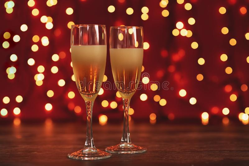 Christmas and New Year celebration with champagne. New Year holiday decorated table. Two Champagne Glasses, vintage toned stock photo