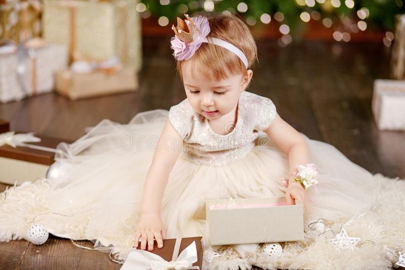 Christmas and New Year celebration concept. Pretty little girl in white dress playing and being happy about christmas tree and royalty free stock photography