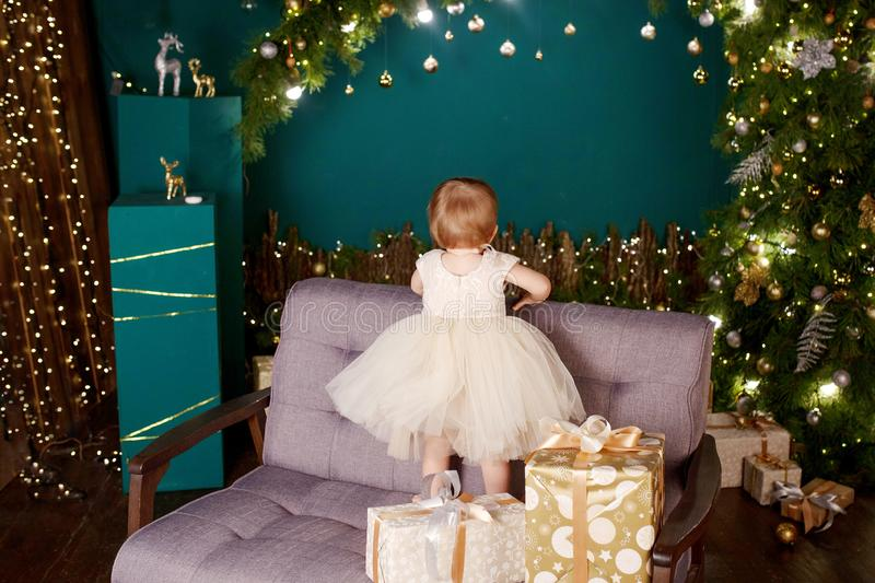 Christmas and New Year celebration concept. Pretty little girl in white dress playing and being happy about christmas tree and. Lights. Winter holidays stock images