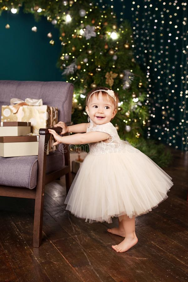 Christmas and New Year celebration concept. Pretty little girl in white dress playing and being happy about christmas tree and. Lights. Winter holidays stock photos