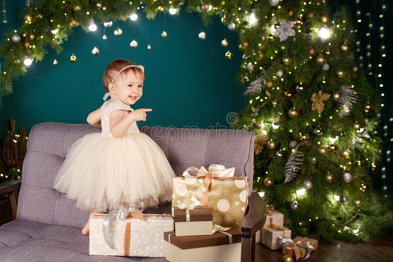 Christmas and New Year celebration concept. Pretty little girl in white dress playing and being happy about christmas tree and. Lights. Winter holidays. Copy royalty free stock photography