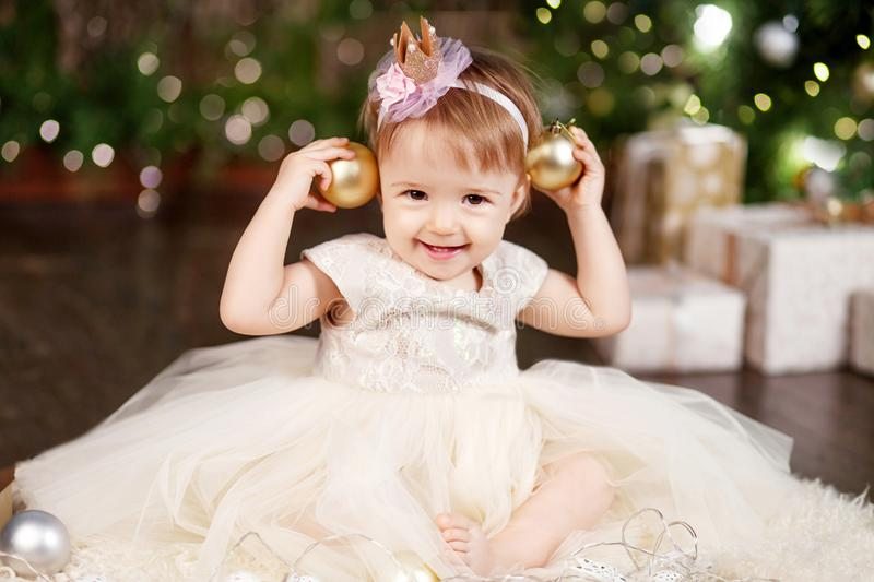 Christmas and New Year celebration concept. Pretty little girl in white dress playing and being happy about christmas tree and stock images
