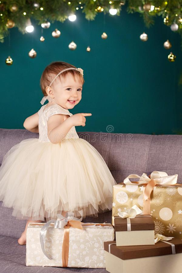 Christmas and New Year celebration concept. Pretty little girl in white dress playing and being happy about christmas tree and stock photography