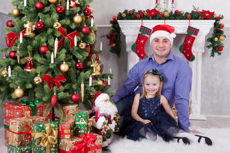Christmas or New year celebration. Father and daughter sit near the Christmas tree. Father have a Santa Claus hat on his head. A f royalty free stock image