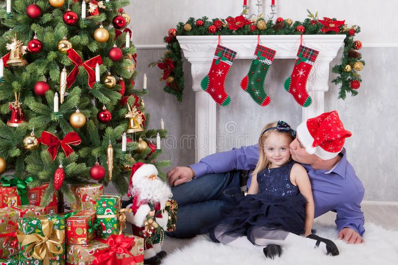 Christmas or New year celebration. Father kisses the daughter near the Christmas tree. Father have a Santa Claus hat on his head. royalty free stock photography