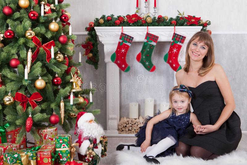 Christmas or New year celebration. Happy mother with her daughter sit near a white fireplace next to a christmas tree royalty free stock image
