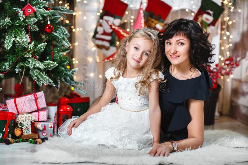 Christmas or New year celebration. Happy mother with her daughter sit near a white fireplace next to a christmas tree. stock photos