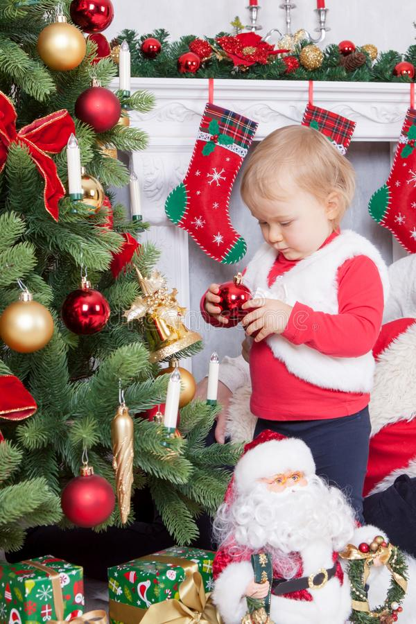Christmas or New year celebration. Little girl in cute red jacket and a fur vest decorating Christmas tree at home near the firepl royalty free stock image