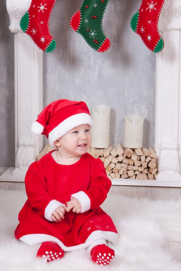 Christmas or New year celebration. Little girl dressed in a red festive suit of gnome and santa hat, sits on the floor near Christ stock photography