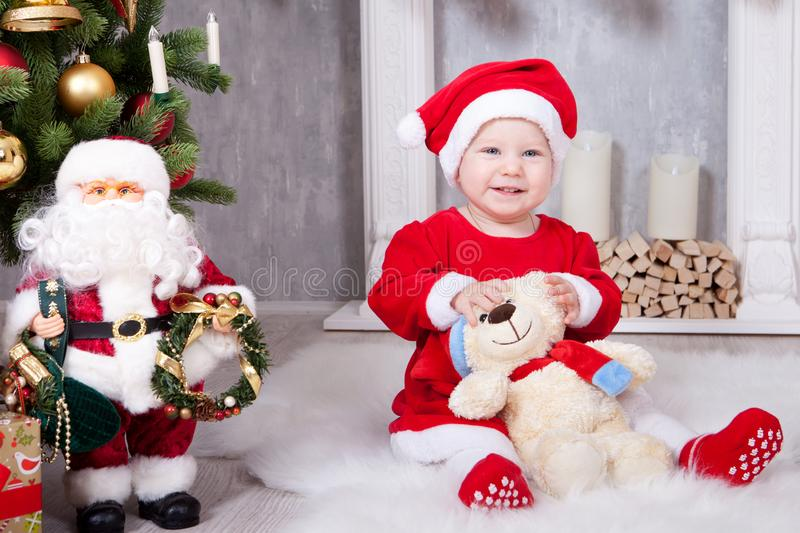 Christmas or New year celebration. Little girl in red dress and santa hat with bear toy sitting on the floor near the Christmas tr royalty free stock photo
