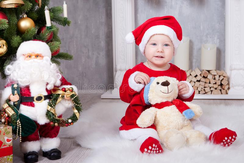 Christmas or New year celebration. Little girl in red dress and santa hat with bear toy sitting on the floor near the Christmas tr royalty free stock image