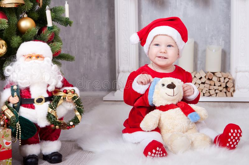 Christmas or New year celebration. Little girl in red dress and santa hat with bear toy sitting on the floor near the Christmas tr stock image