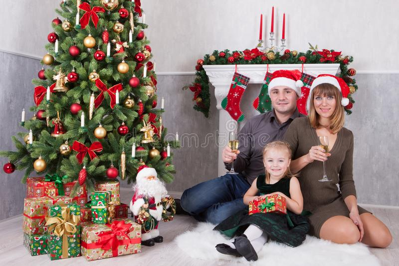 Christmas or New year celebration. Portrait of cheerful happy family of three people celebrates with xmas gifts near Christmas tre royalty free stock photos