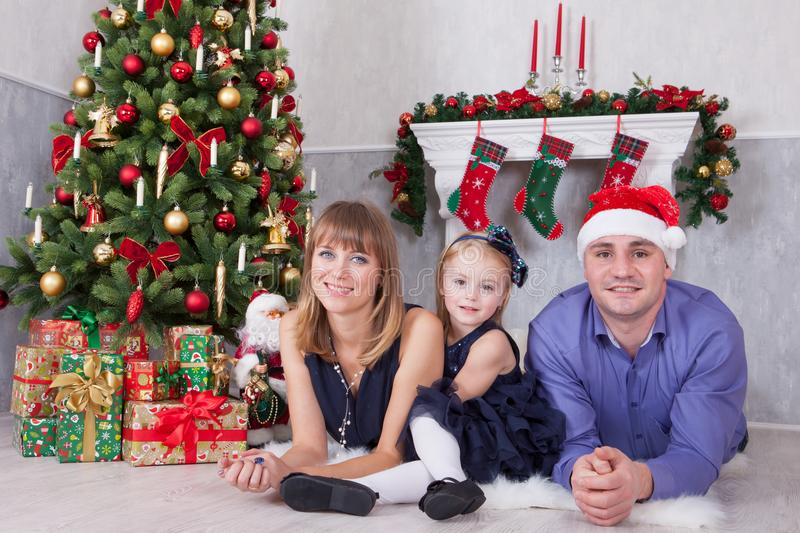 Christmas or New year celebration. Portrait of cheerful happy family of three people lying on the floor near Christmas tree with x royalty free stock photography