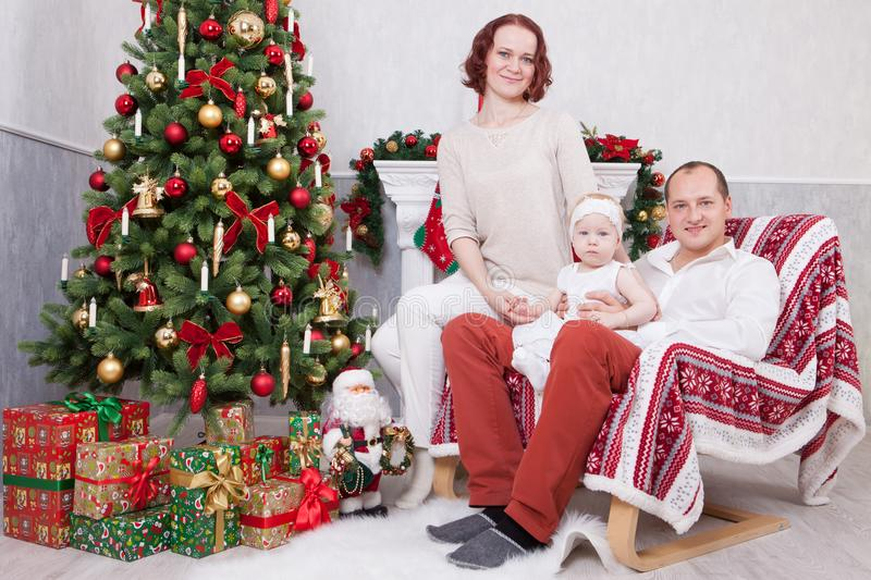 Christmas or New year celebration. Portrait of cheerful young family of three people near the Christmas tree with xmas gifts. A fi stock image