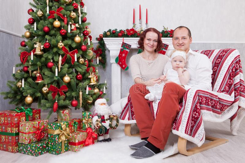 Christmas or New year celebration. Portrait of cheerful young family of three people near the Christmas tree with xmas gifts. A fi. Replace with christmas royalty free stock photos