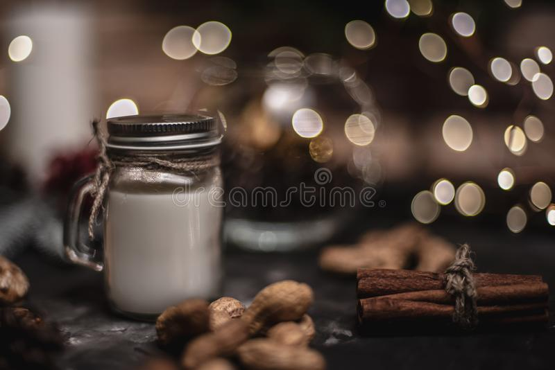 Christmas and new year decoration background with round bokeh garland, cinnamon, cookies, cones, nuts and candle in cup royalty free stock images