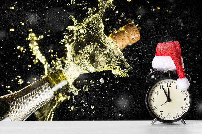 Christmas or New Year celebration theme with explosion of splashing champagne sparkling wine near vintage alarm clock with Santa royalty free stock photography