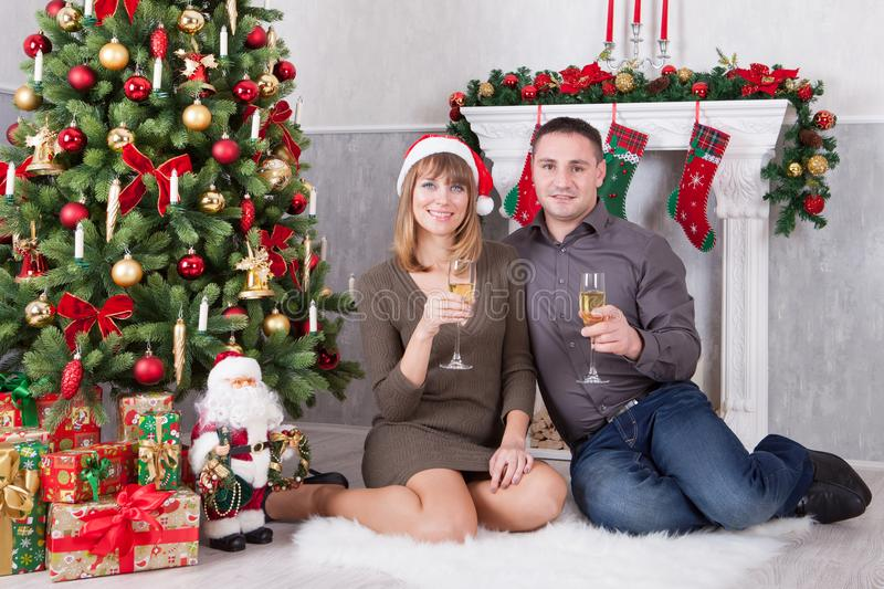 Christmas or New year celebration. Young beautiful couple with a glass of champagne sitting near Christmas tree with xmas gifts. A royalty free stock photography