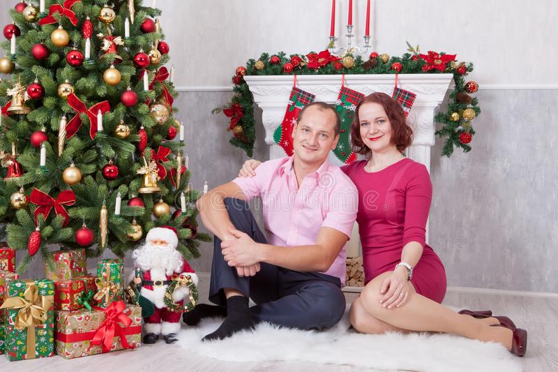 Christmas or New year celebration. Young couple sit and embrace in Christmas interior, near the fireplace, Christmas tree. Happy h stock photos