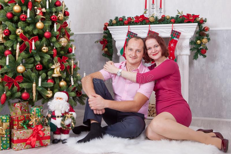 Christmas or New year celebration. Young couple sit and embrace in Christmas interior, near the fireplace, Christmas tree. Happy h royalty free stock images