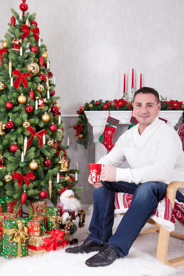 Christmas or New year celebration. Young man sits in a armchair and holds a cup near Christmas tree with xmas gifts. A fireplace w stock image