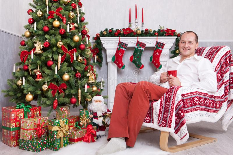 Christmas or New year celebration. Young man sits in a armchair and holds a cup near Christmas tree with xmas gifts. A fireplace w stock photography