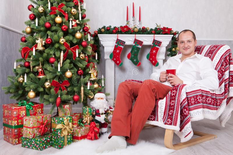 Christmas or New year celebration. Young man sits in a armchair and holds a cup near Christmas tree with xmas gifts. A fireplace w royalty free stock photography