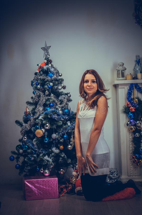 Christmas or New year 2020 celebration. Young woman in a festive white dress sits near the Christmas tree at home royalty free stock image
