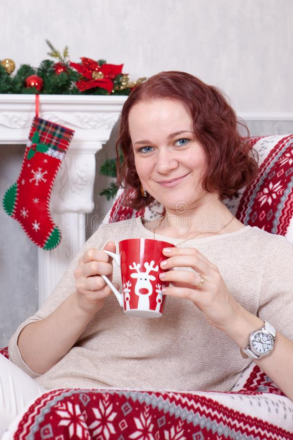 Christmas or New year celebration. Young woman in a white knitted jumper holds a cup in hand and sitting in a chair in stock image