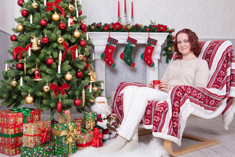Christmas or New year celebration. Young woman in a white knitted jumper holds a cup in hand and sitting in a chair in a Christmas stock image