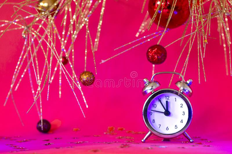 Christmas or New Year composition with alarm clock and beautiful gold decorations on red neon background, Xmas countdown royalty free stock photography