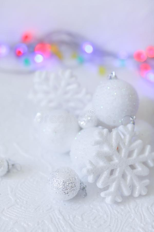New year or Christmas decorations in silver and white colors with balls, snowflakes and garland bokeh royalty free stock images