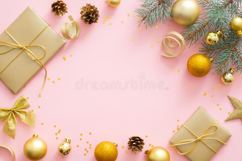Christmas or New year composition. Christmas presents, ribbon, golden balls, fir tree branches on pastel pink background. Flat lay stock photos