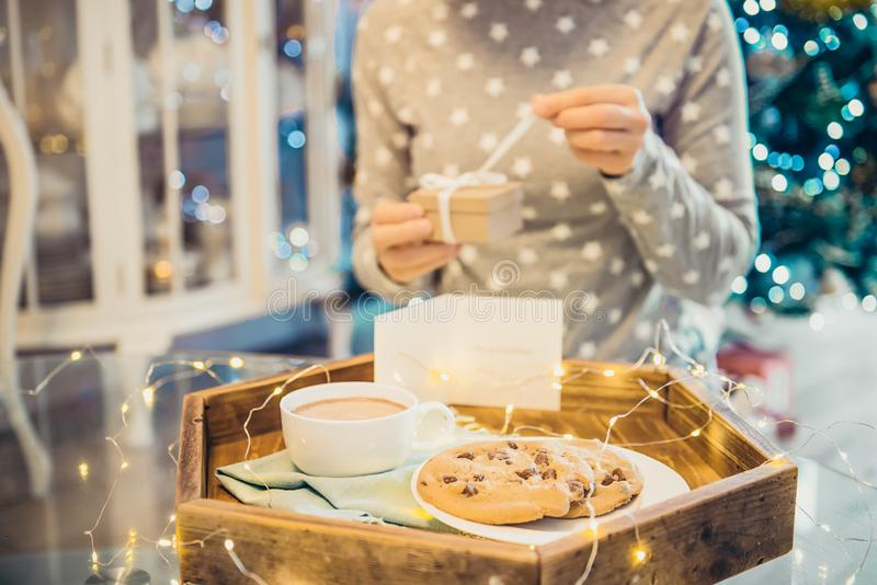 Christmas and New Year composition. Cocoa and cookies on the wooden tray and blurred no face woman opening her present on xmas royalty free stock photos