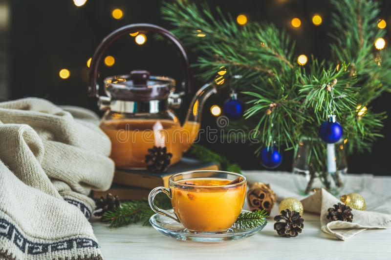Christmas and New Year composition. Cup and teapot of hot spicy tea with sea buckthorn, jam in the glass jar, branches of pine and. Spruce, holiday decor, bokeh royalty free stock photos