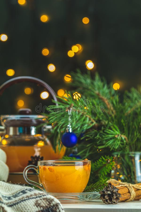 Christmas and New Year composition. Cup and teapot of hot spicy tea with sea buckthorn. Jam in the glass jar, branches of pine and spruce, holiday decor, bokeh stock photo