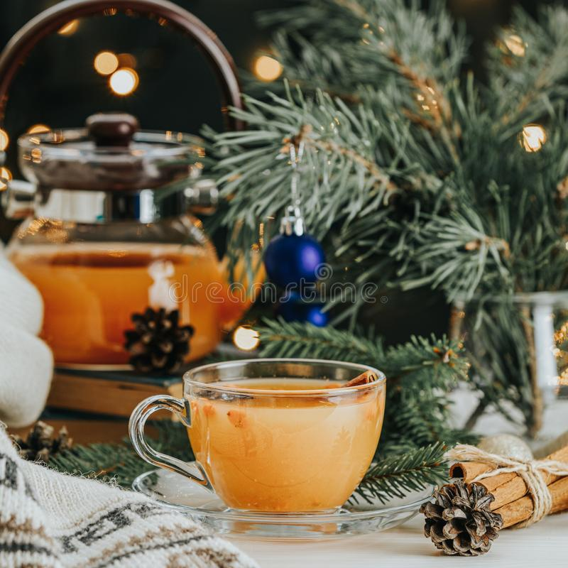 Christmas and New Year composition. Cup and teapot of hot spicy tea with sea buckthorn royalty free stock photos