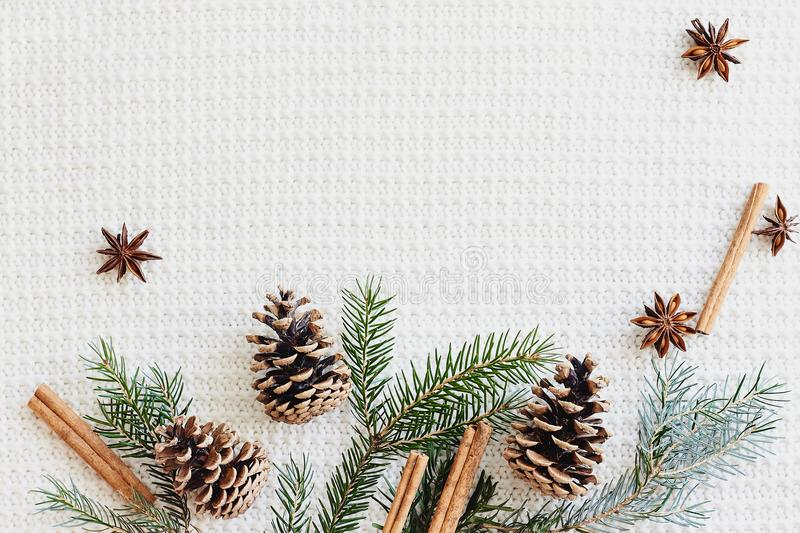 Christmas and New Year composition. Fir branches with cones, star anise, cinnamon on knitted white background royalty free stock photo